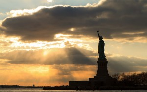Statue of Liberty silhouetted by sun breaking through clouds